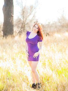 Рыжеволосая красотка с большими сиськами и бритой писькой позирует на лесной лужайке