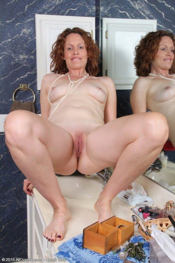 Пухлая зрелая красотка с большими дойками показывает голую жопу и пизду